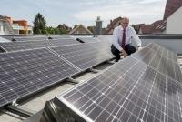Heinz Jörg Göbert auf dem Flachdach seines Bungalows inmitten von 74 Photovoltaikmodulen.<br />Bilder: Panasonic